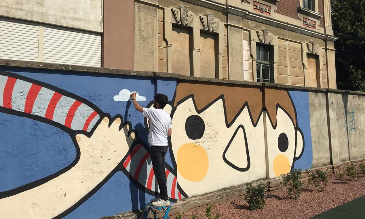 Ale Puro creating one of his murals