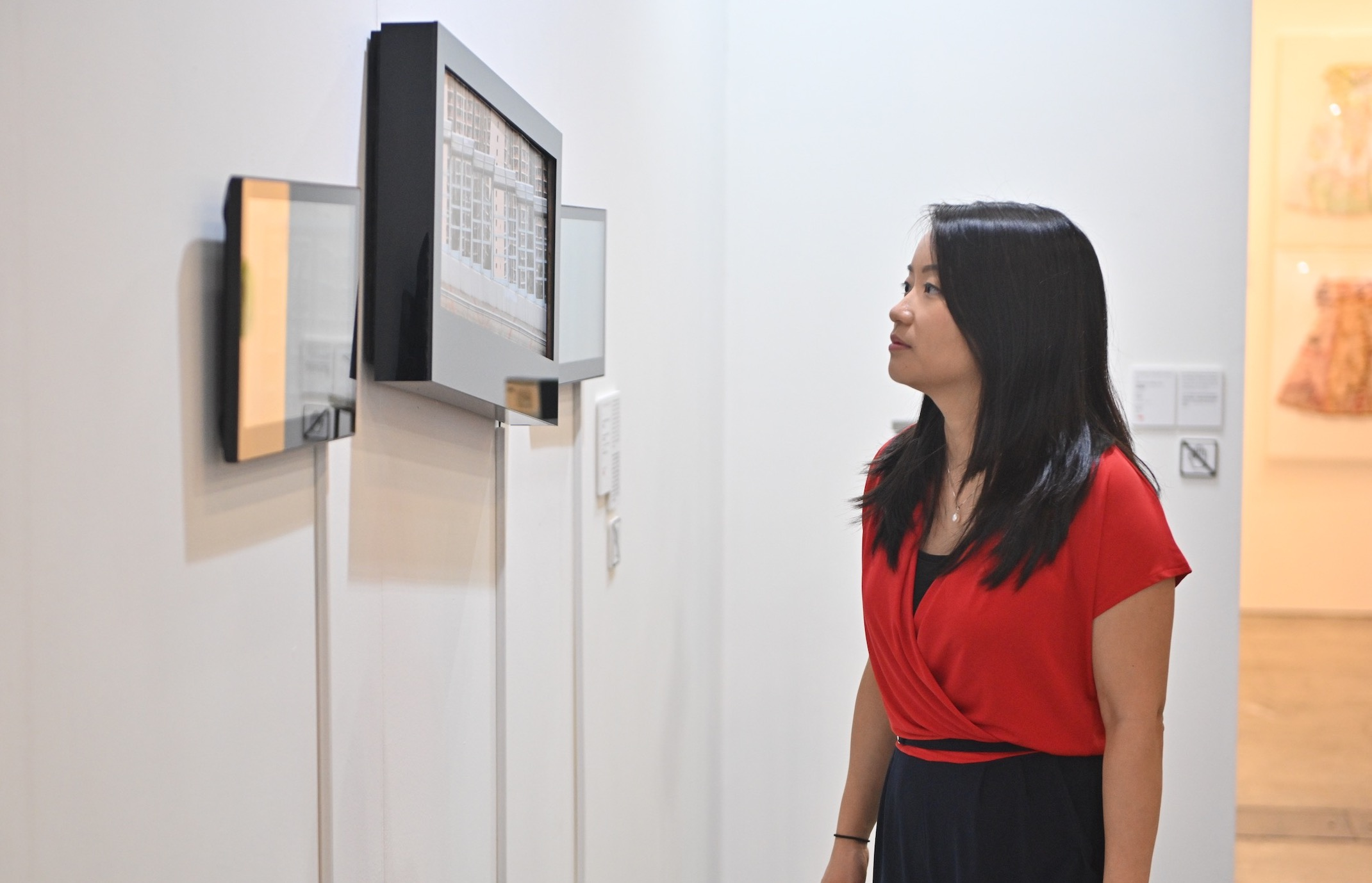 May Wong looking at the Young Talent exhibition