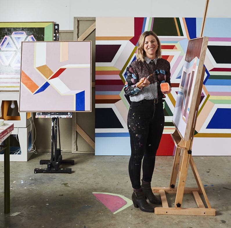 Jasmine Mansbridge at work, creating one of her colourful geometric paintings