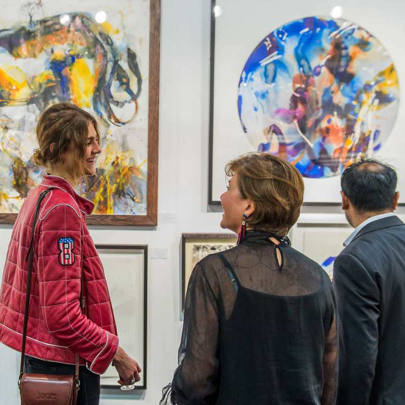 A visitor purchases an artwork at Affordable Art Fair Battersea